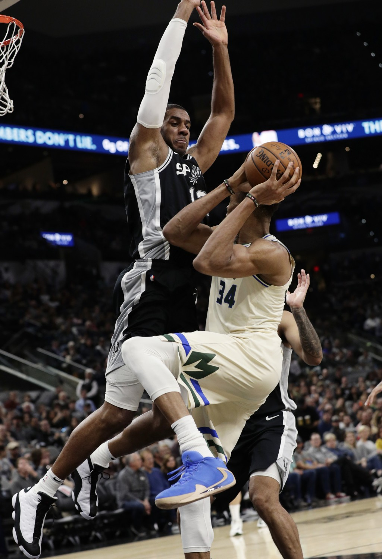 San Antonio Spurs center LaMarcus Aldridge, top, pressures Milwaukee Bucks forward Giannis Antetokounmpo (34) during the second half of an NBA basketb...