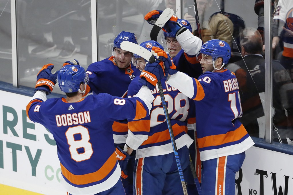 New York Islanders left wing Anders Lee (27), second from right with his back against the glass, celebrates with teammates, including defenseman Noah ...