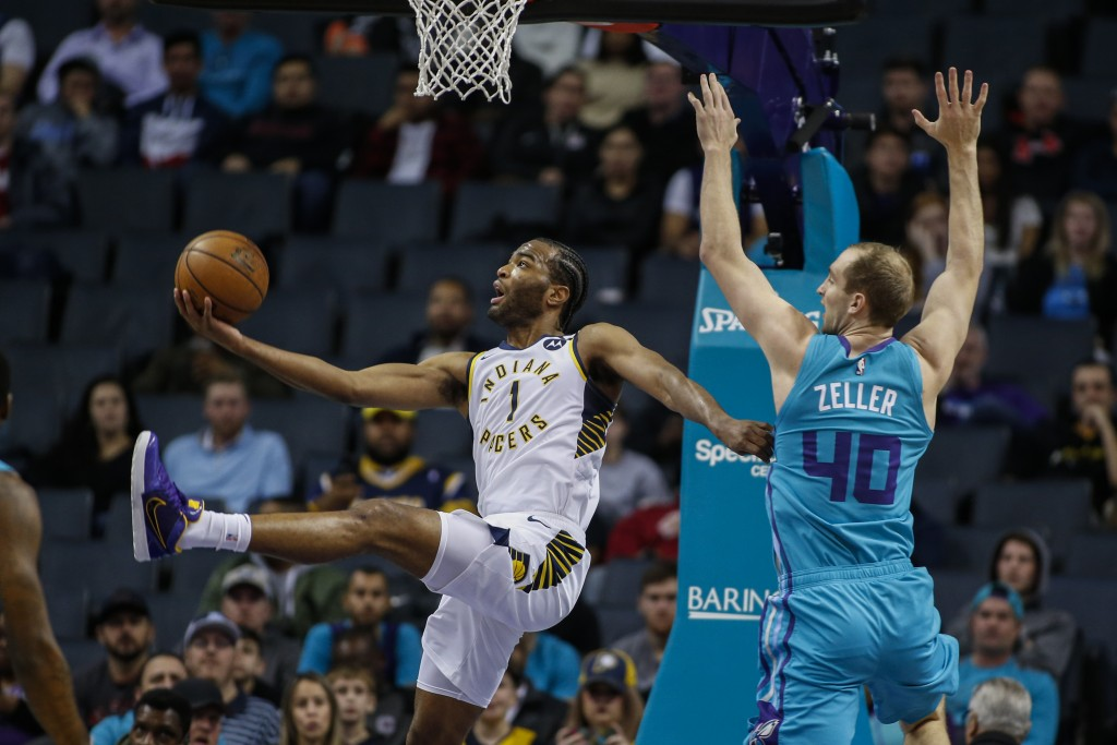 Indiana Pacers forward T.J. Warren, left, shoots a scoop shot as he drives past Charlotte Hornets forward Cody Zeller in the first half of an NBA bask...