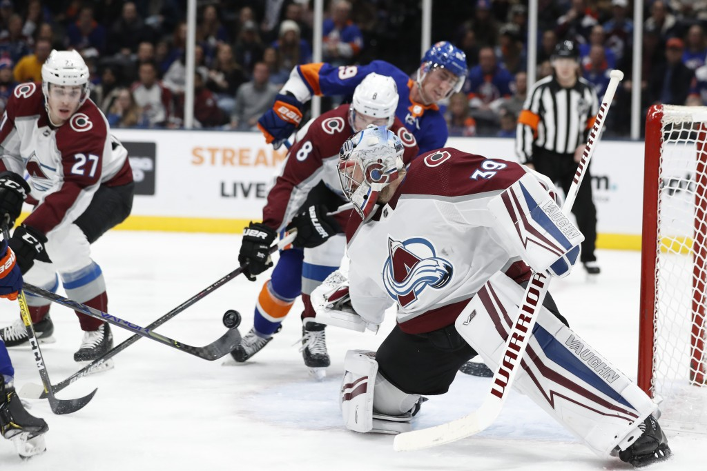 Colorado Avalanche goaltender Pavel Francouz (39) keeps his eye on the puck as it bounces off the stick of an Islanders player during the second perio...