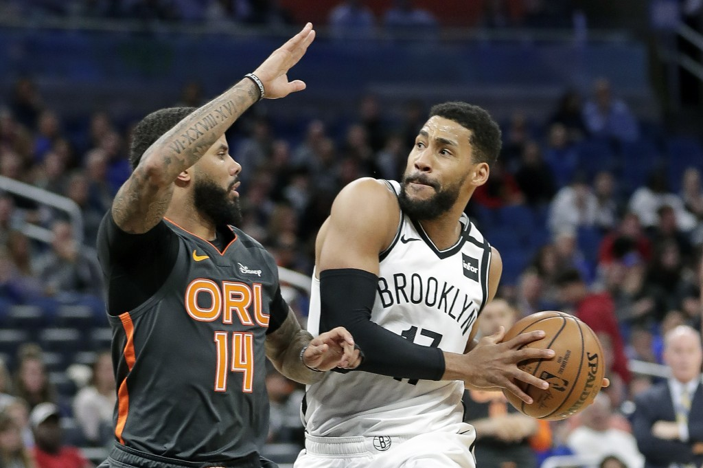 Brooklyn Nets guard Garrett Temple, right, looks to shoot over Orlando Magic guard D.J. Augustin (14) during the second half of an NBA basketball game...