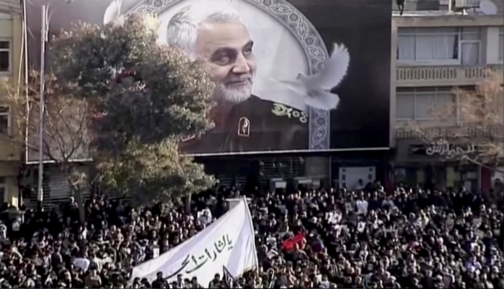 In this image made from a video, mourners gather to pay their respects to the slain Gen. Qassem Soleimani who was killed in a U.S. airstrike, in Kerma...