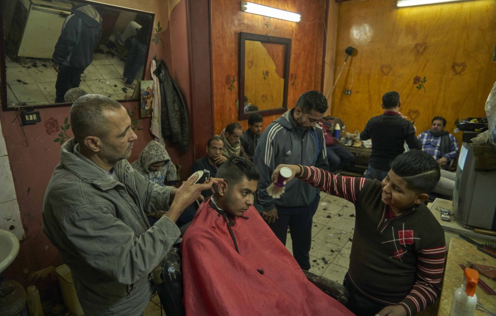 Men wait at a barber shop for their turn to get a haircut, in preparation for the Coptic Christmas celebration, at a residential and industrial area o...