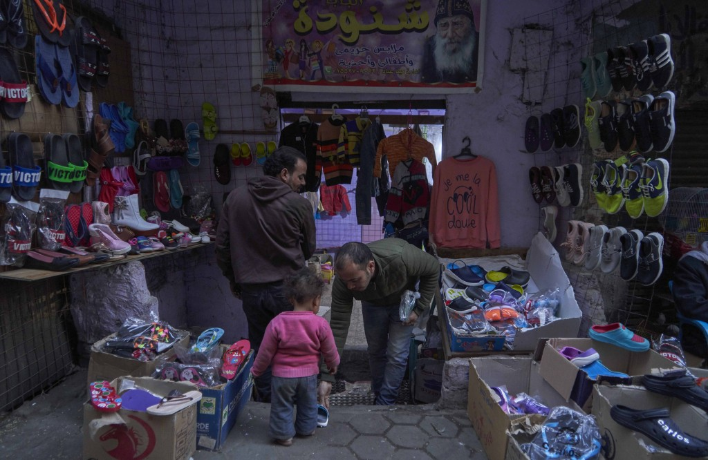 A child tries on new shoes at a street shop display for customers to buy new shoes and clothing, in preparation for the Coptic Christmas celebration, ...
