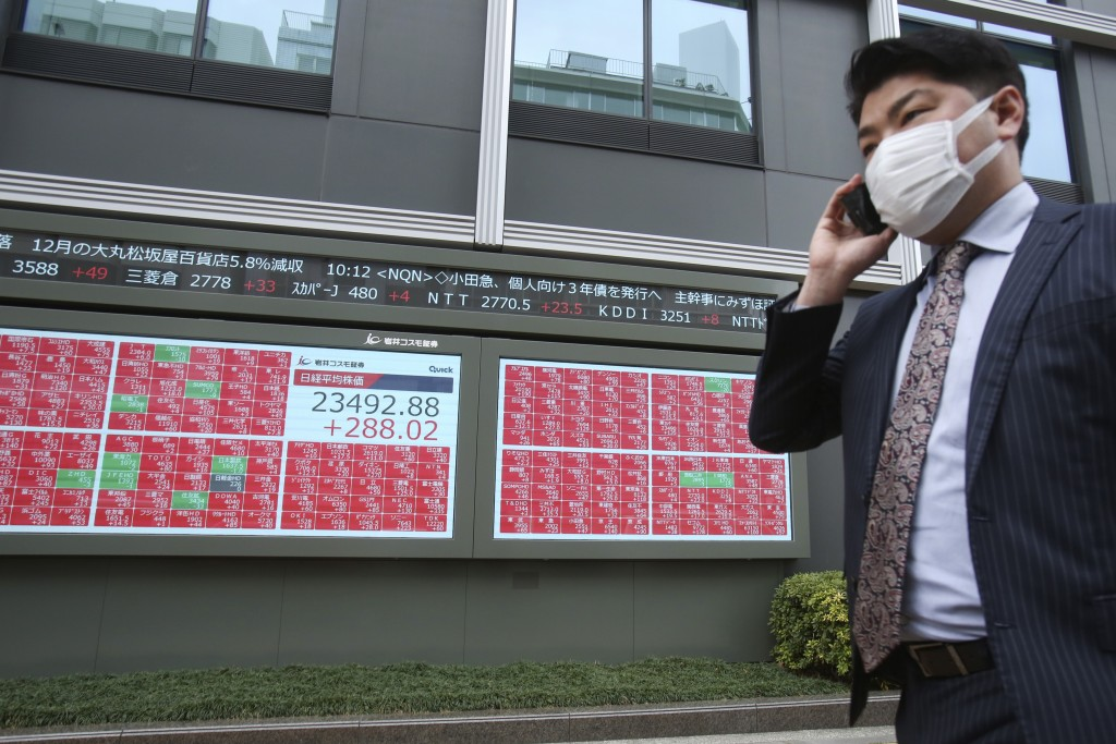 A man walks by an electronic stock board of a securities firm in Tokyo, Tuesday, Jan. 7, 2020. Shares are climbing in Asia following modest gains on W...
