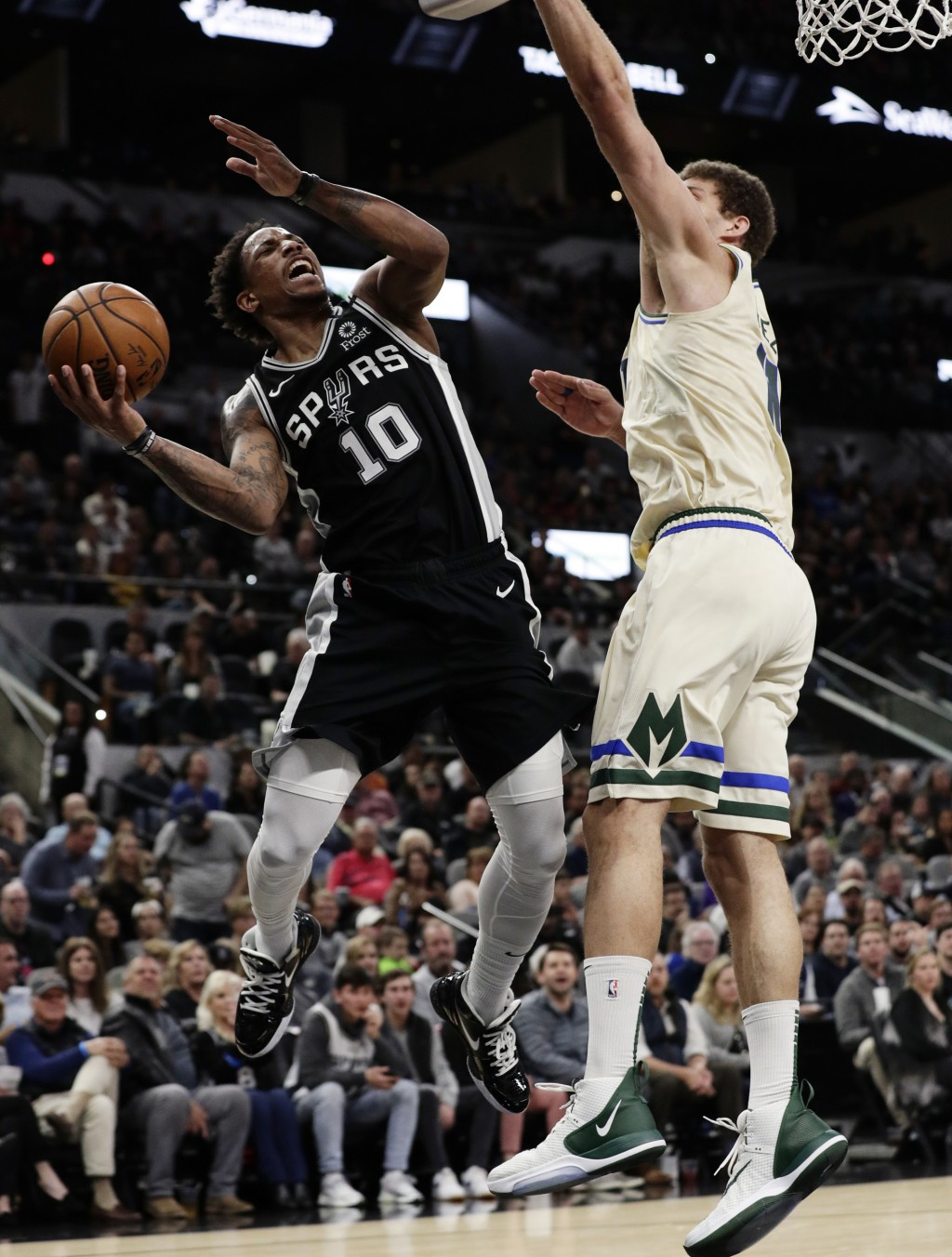 San Antonio Spurs guard DeMar DeRozan (10) is fouled by Milwaukee Bucks center Brook Lopez (11) during the first half of an NBA basketball game in San...