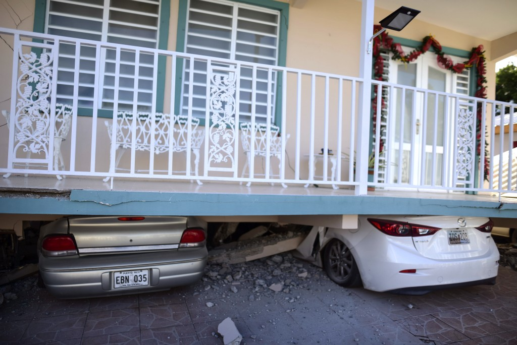 Cars are crushed under a home that collapsed after an earthquake hit Guanica, Puerto Rico, Monday, Jan. 6, 2020. A 5.8-magnitude quake hit Puerto Rico...