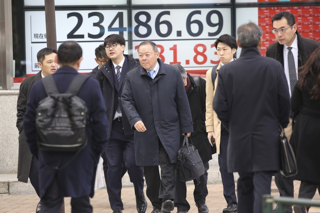 People walk by an electronic stock board of a securities firm in Tokyo, Tuesday, Jan. 7, 2020. Shares are climbing in Asia following modest gains on W...