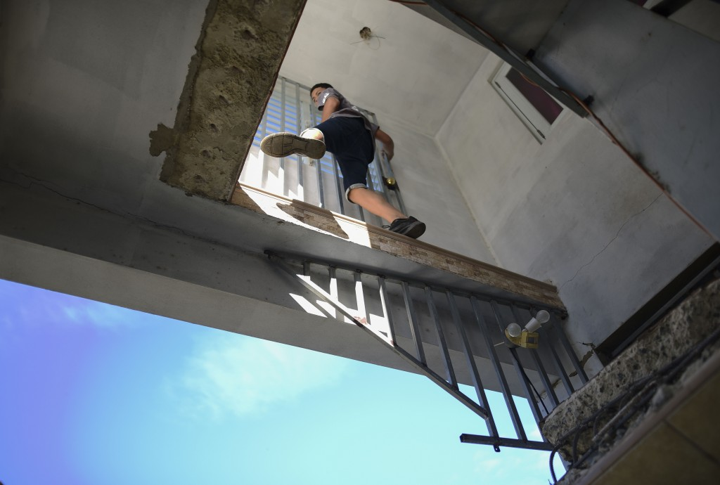 A youth climbs into his aunt's damaged home where the stairs into the living room collapsed after an earthquake hit Guanica, Puerto Rico, Monday, Jan....