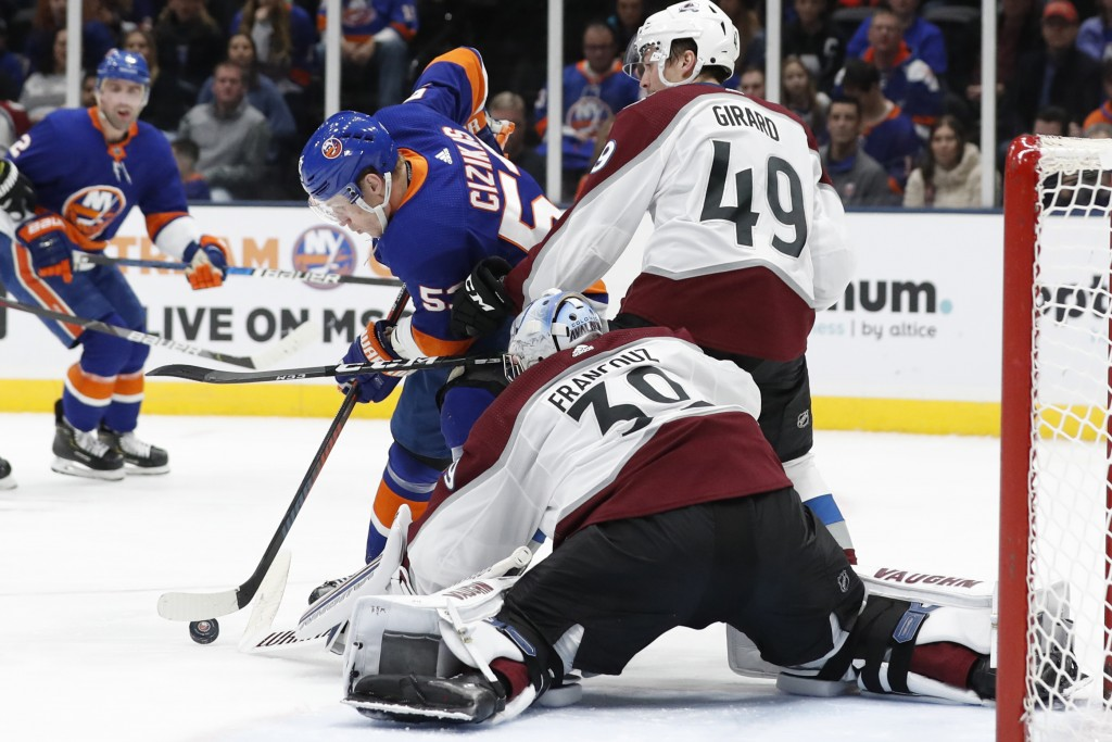 Colorado Avalanche defenseman Samuel Girard (49) defends New York Islanders center Casey Cizikas (53) who tries to maneuver the puck in front of Avala...