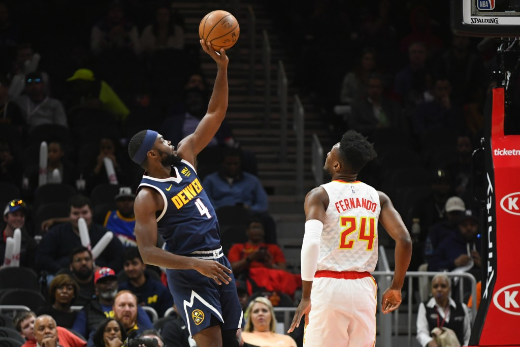 Denver Nuggets forward Paul Millsap (4) shoots one-handed in front of Atlanta Hawks forward Bruno Fernando during an NBA basketball game Monday, Jan. ...
