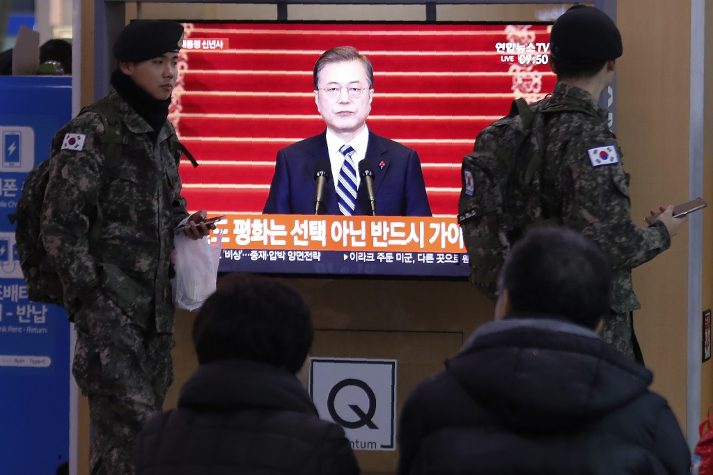 South Korean army soldiers pass by a TV screen showing the live broadcast of South Korean President Moon Jae-in's New Year's speech at the Seoul Railw...