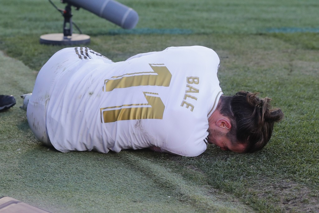 Real Madrid's Gareth Bale lies on the pitch after a tackle during a Spanish La Liga soccer match between Getafe and Real Madrid at the Coliseum Alfons...