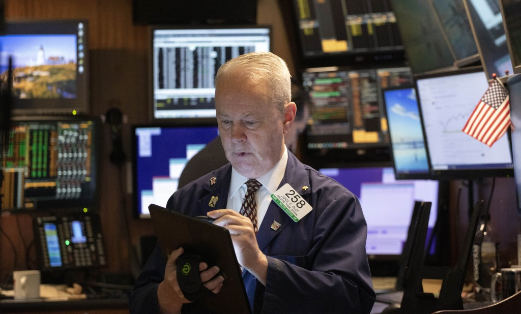 FILE - In this Jan. 2, 2020, file photo James Riley monitors stock prices at the New York Stock Exchange. Global stocks stabilized Tuesday, Jan. 7, an...