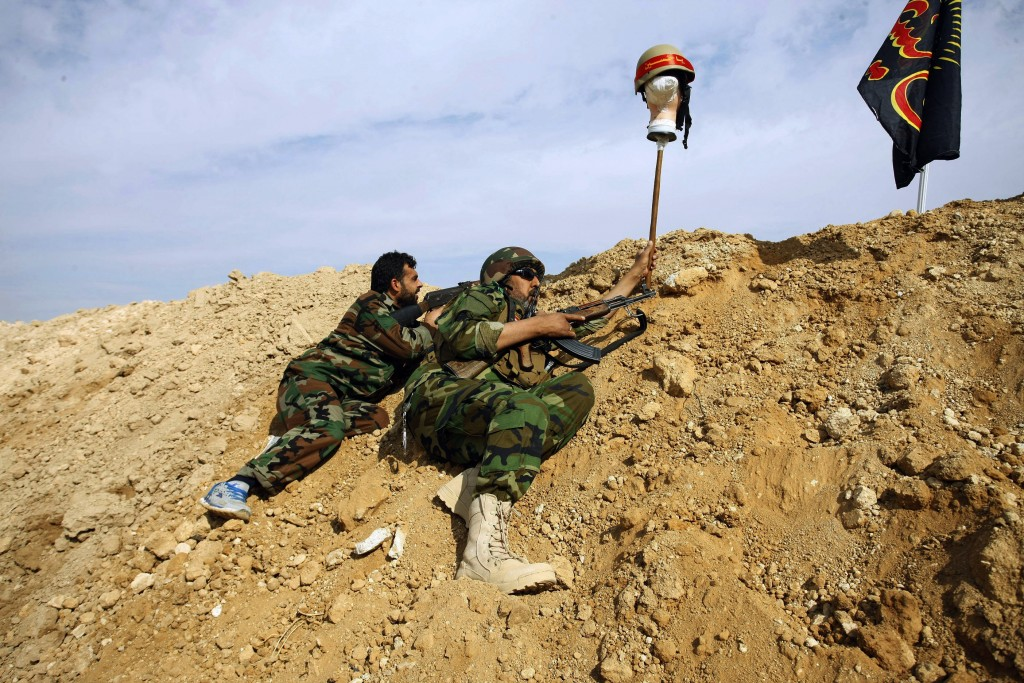 FILE - In this Nov. 22, 2013 file photo, Iraqi and Lebanese Shiite fighters from a group called the Hussein Brigade, loyal to Syria's President Bashar...