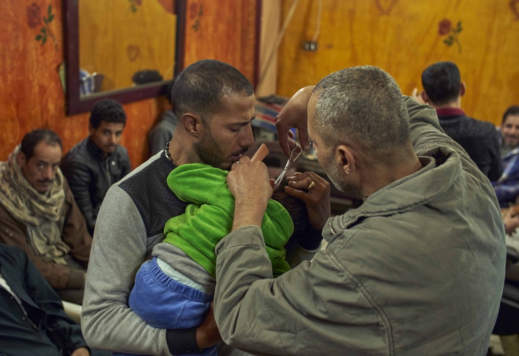 Romany, a Coptic man, left, holds his four-year-old son, for Eissa the barber to cut his hair, in preparation for the Coptic Christmas celebration, at...