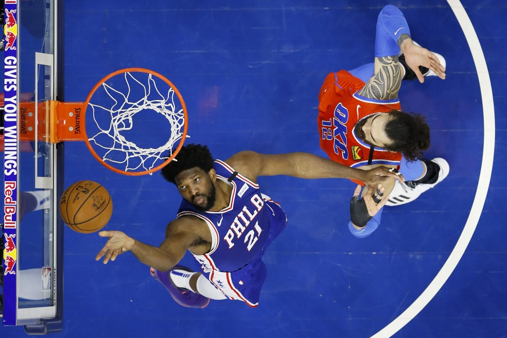 Philadelphia 76ers' Joel Embiid, left, goes up to shoot against Oklahoma City Thunder's Steven Adams during the first half of an NBA basketball game, ...