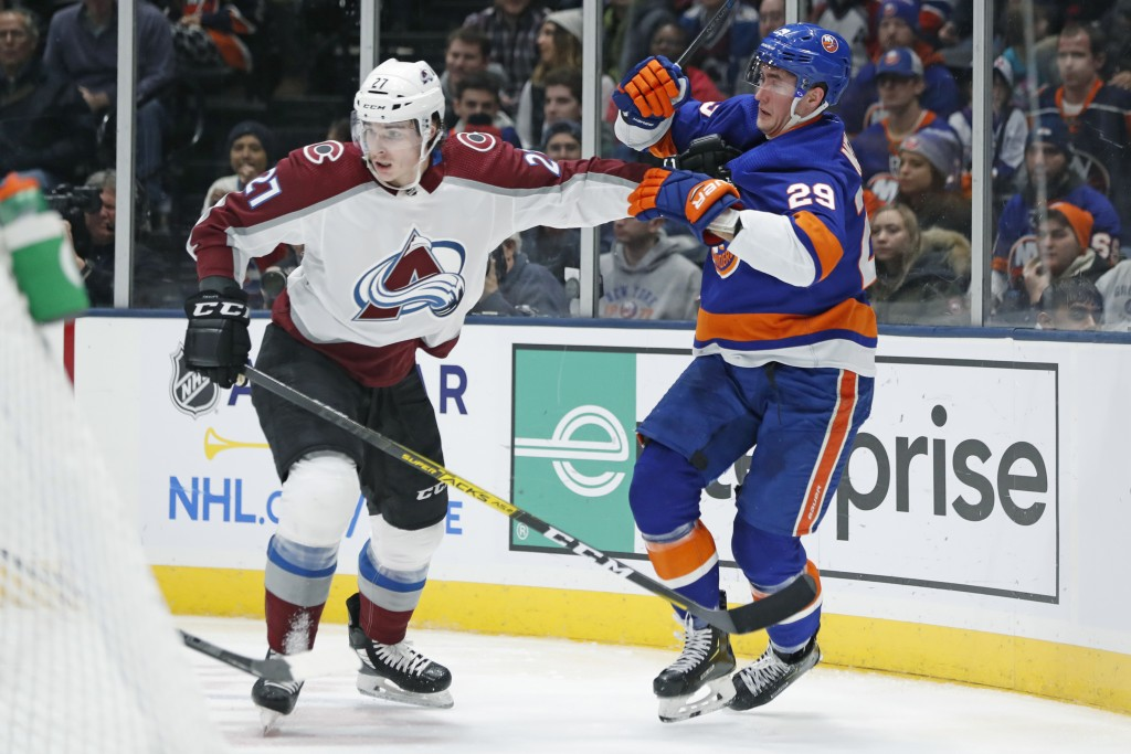 Colorado Avalanche defenseman Ryan Graves (27) fends off New York Islanders center Brock Nelson (29) during the second period of an NHL hockey game, M...
