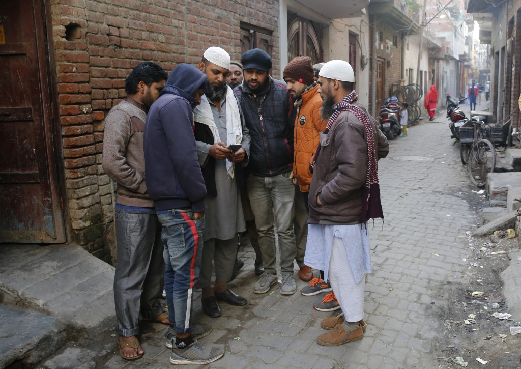 In this Tuesday, Dec. 24, 2019, photo, relatives of Mohammad Asif who was shot and killed during protests against Citizenship Amendment Act, show a pi...