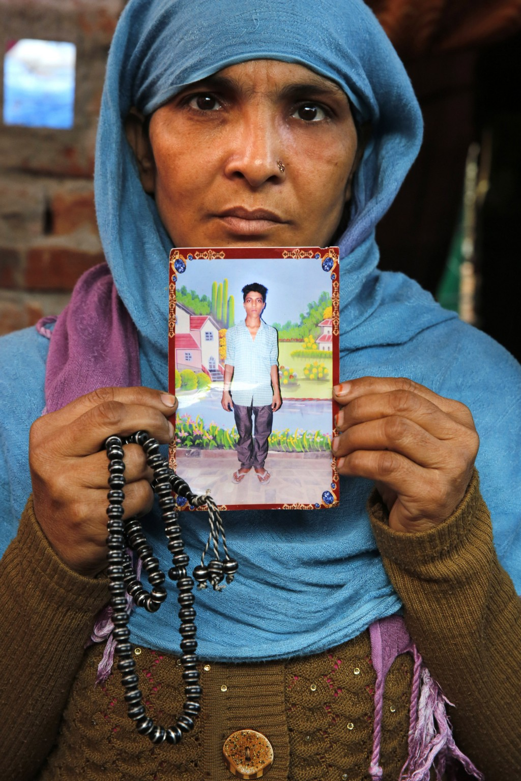 In this Tuesday, Dec. 24, 2019, photo, the mother of Mohammad Asif who was shot and killed during protests against Citizenship Amendment Act, holds a ...