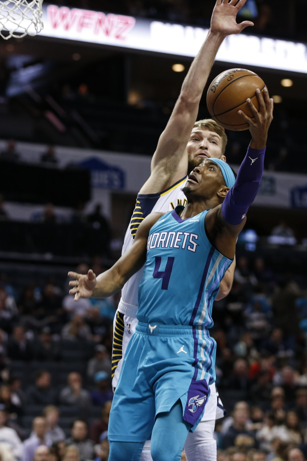 Charlotte Hornets guard Devonte' Graham (4) shoots against Indiana Pacers forward Domantas Sabonis in the first half of an NBA basketball game in Char...