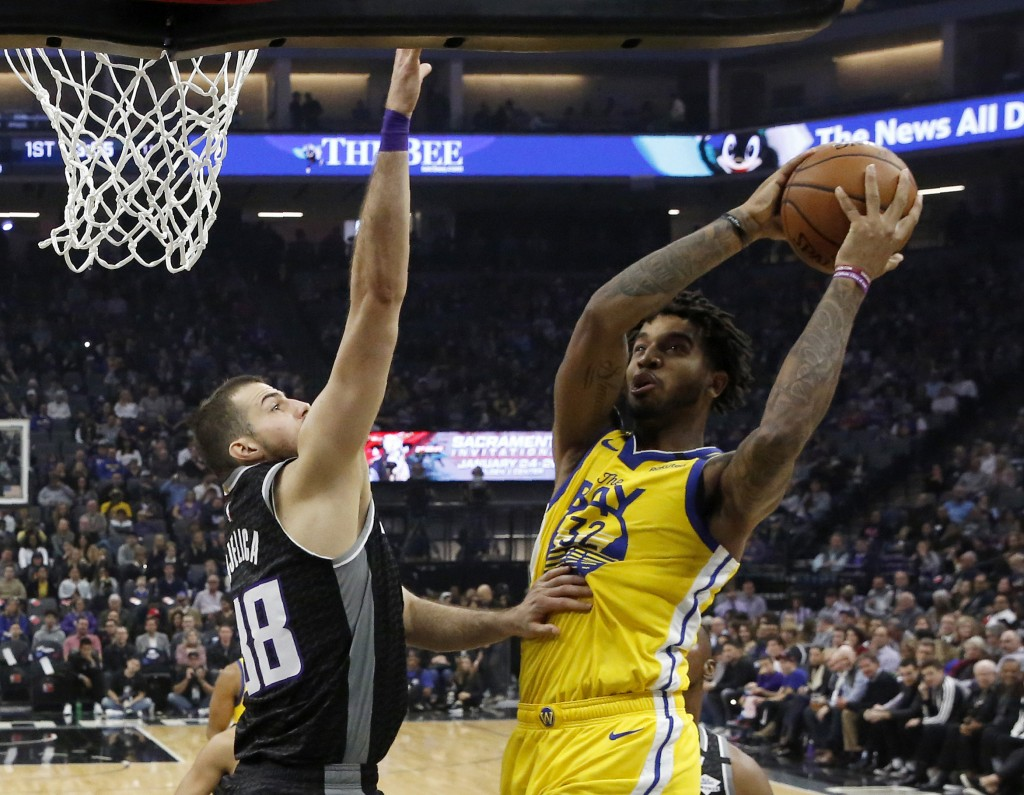 Golden State Warriors forward Marquese Chriss, right, goes to the basket against Sacramento Kings forward Nemanja Bjelica during the first quarter of ...