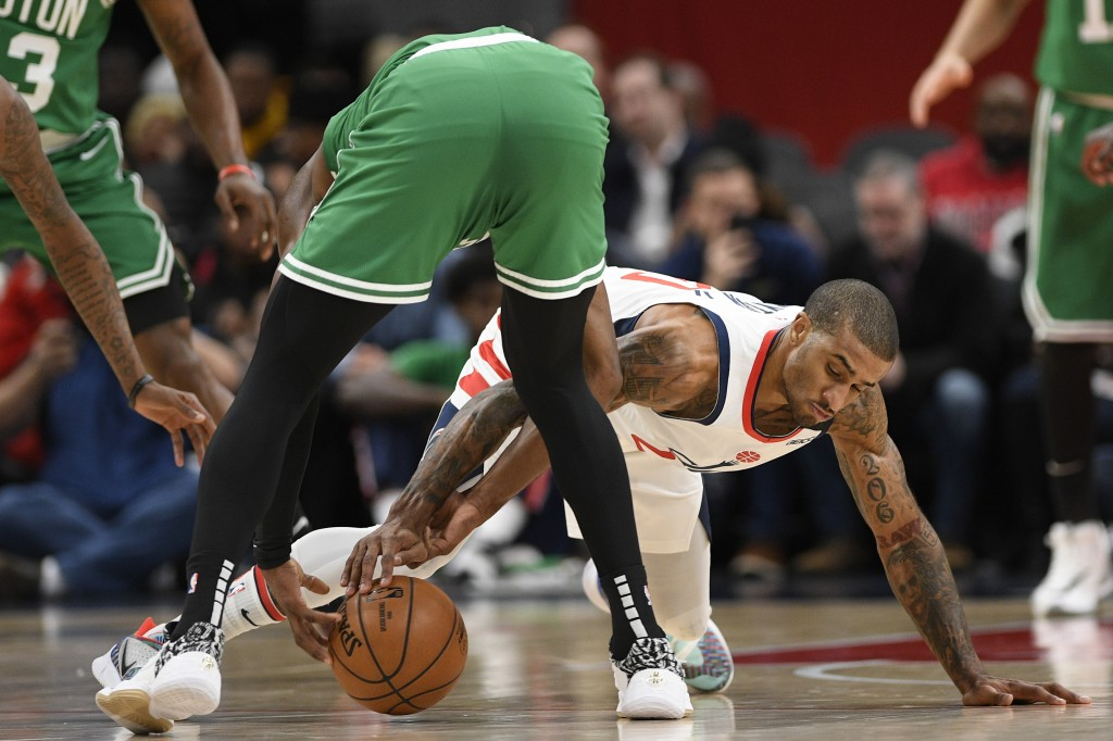 Washington Wizards guard Gary Payton II, right, and Boston Celtics guard Jaylen Brown, left, battle for the ball during the first half of an NBA baske...
