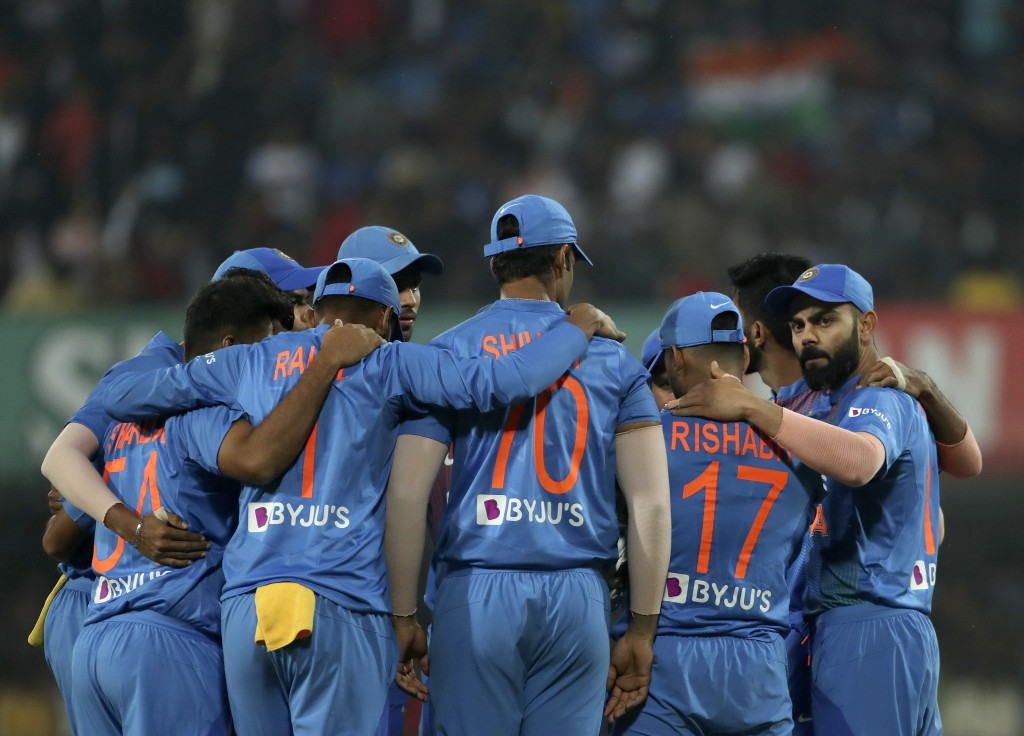 India's captain Virat Kohli, right, and teammates stand in a huddle before the start of the second Twenty20 international cricket match between India ...