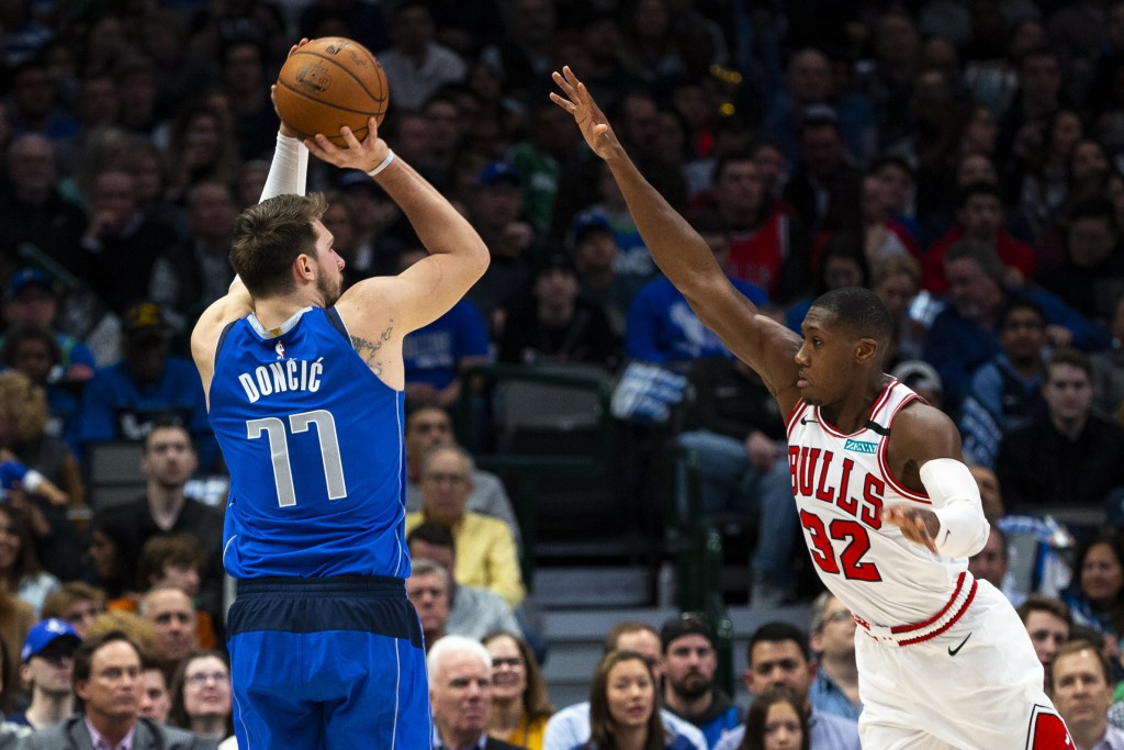 Dallas Mavericks forward Luka Doncic (77) attempts to shoot as Chicago Bulls guard Kris Dunn (32) defends during the first half of an NBA basketball g...