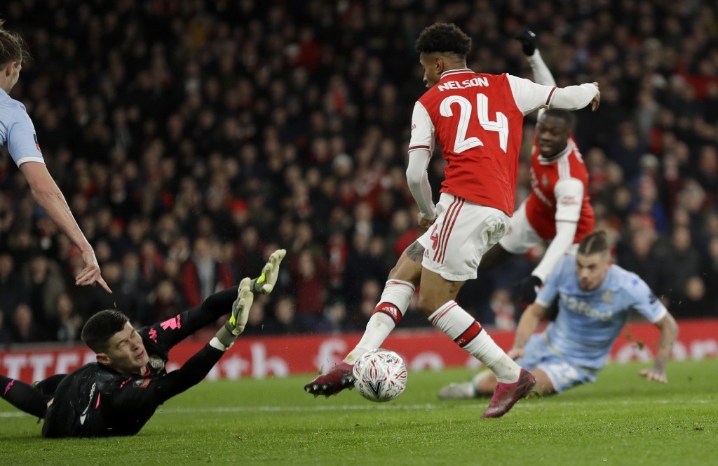 Arsenal's Reiss Nelson shoots on goal to score his side's first goal during the English FA Cup soccer match between Arsenal and Leeds United at the Em...