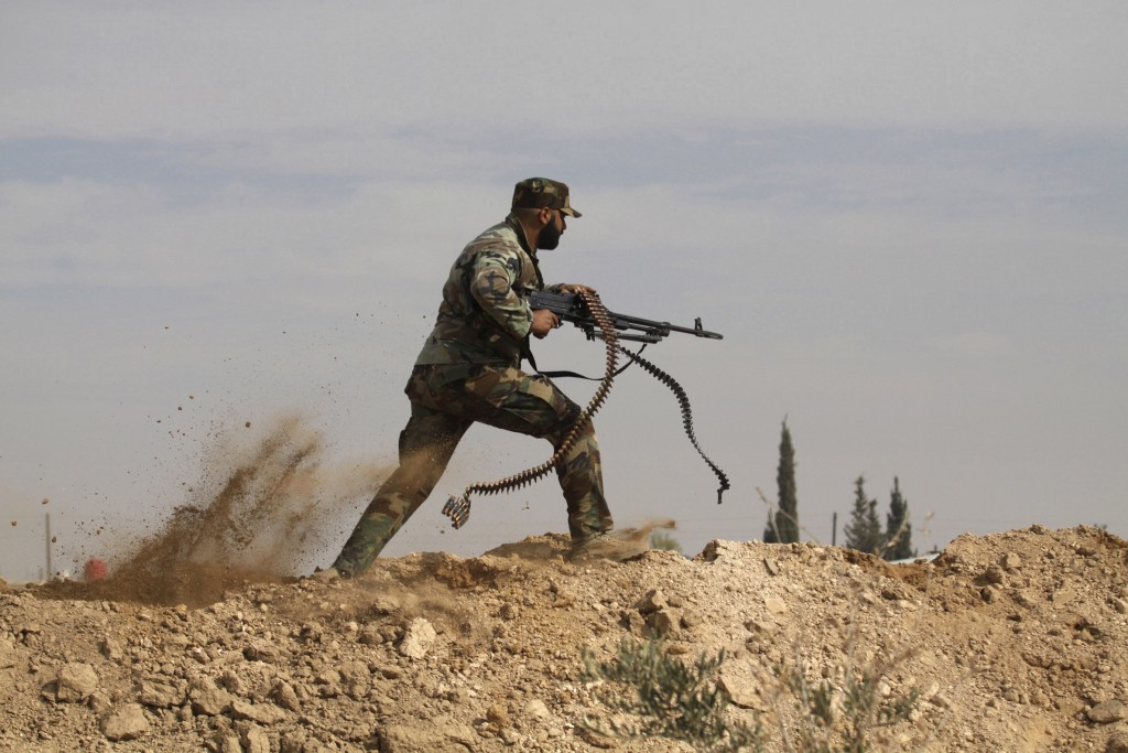FILE - In this Nov. 22, 2013 file photo, a Shiite fighter clashes with members of the Sunni-dominated Free Syrian Army rebels in the town of Hatita, S...