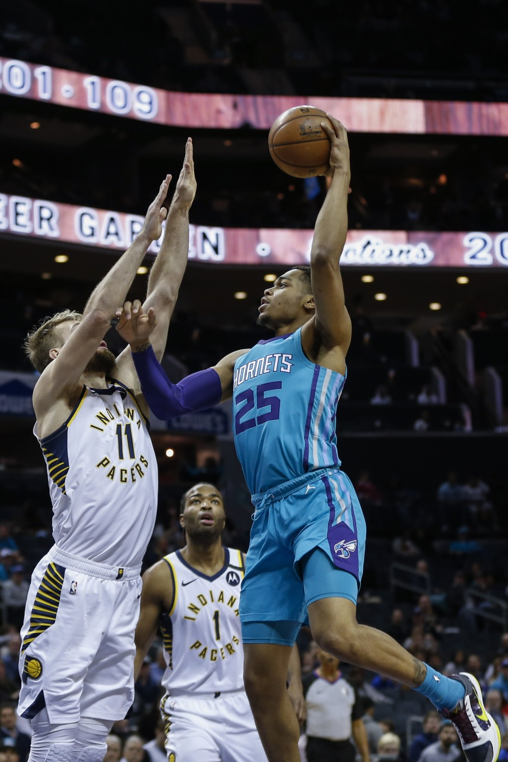 Charlotte Hornets forward P.J. Washington, right, shoots over Indiana Pacers forward Domantas Sabonis in the first half of an NBA basketball game in C...