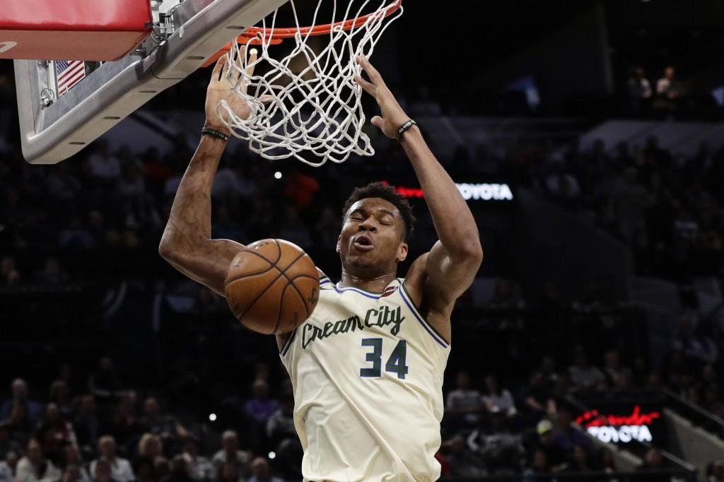 Milwaukee Bucks forward Giannis Antetokounmpo (34) scores against the San Antonio Spurs during the first half of an NBA basketball game in San Antonio...