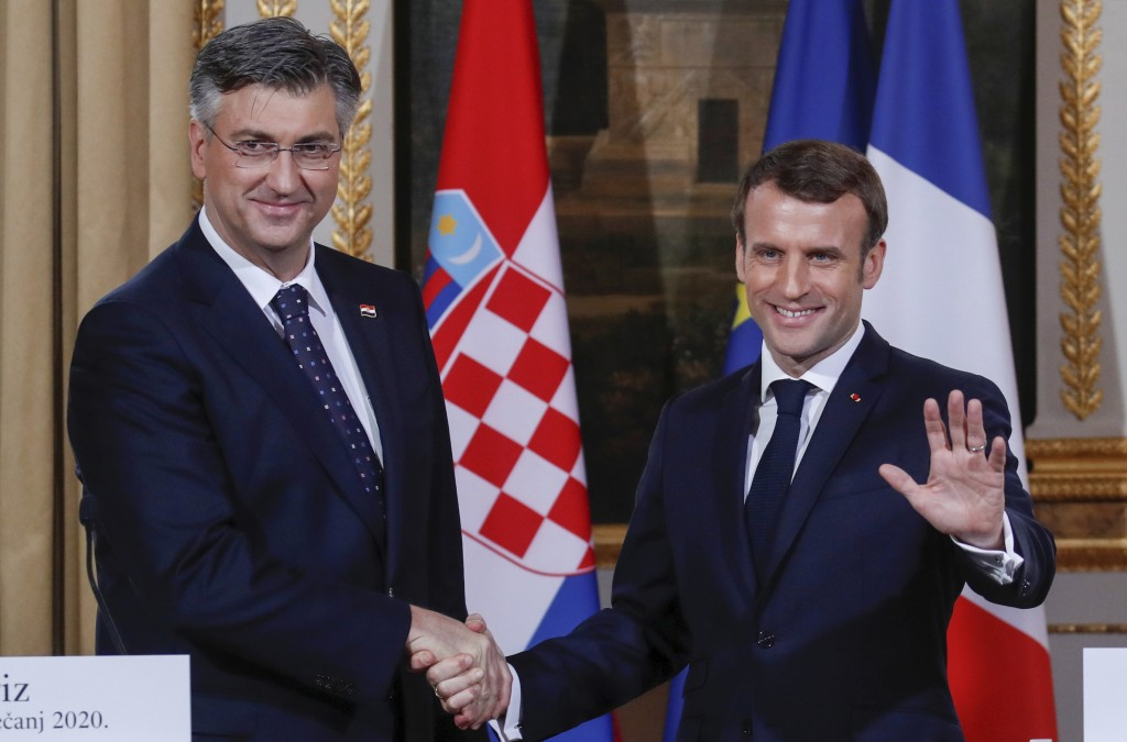 French President Emmanuel Macron, right, shakes hands with Croatian Prime Minister Andrej Plenkovic at the Elysee Palace in Paris, Tuesday, Jan. 7, 20...