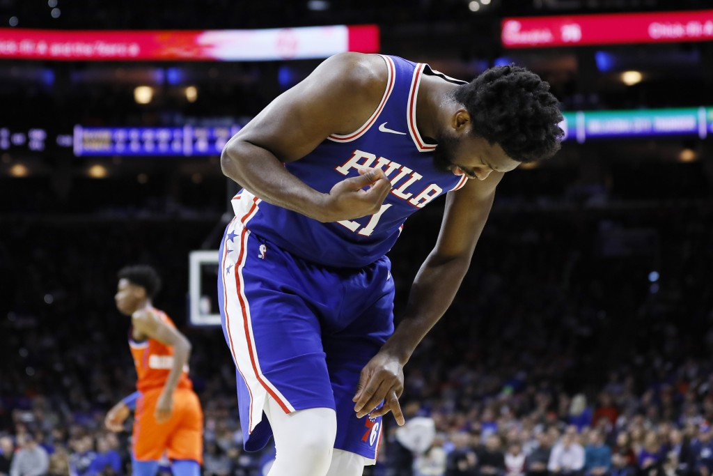 Philadelphia 76ers' Joel Embiid looks at his injured finger during the first half of an NBA basketball game against the Oklahoma City Thunder, Monday,...