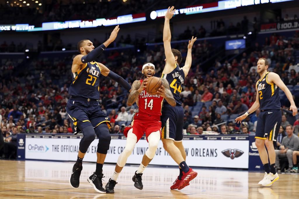 New Orleans Pelicans forward Brandon Ingram (14) drives between Utah Jazz center Rudy Gobert (27) and forward Bojan Bogdanovic (44) in the first half ...