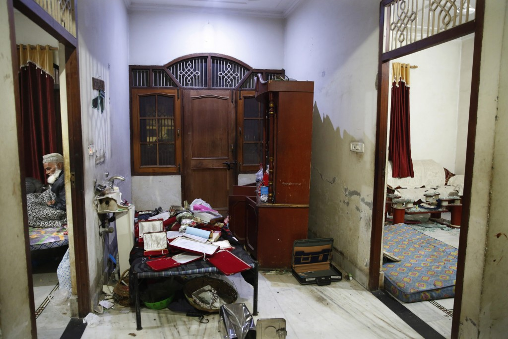 In this Tuesday, Dec. 24, 2019, photo, Anwar Ilahi, 74, sits next to a vandalized room of his house allegedly by the police after protests against Cit...