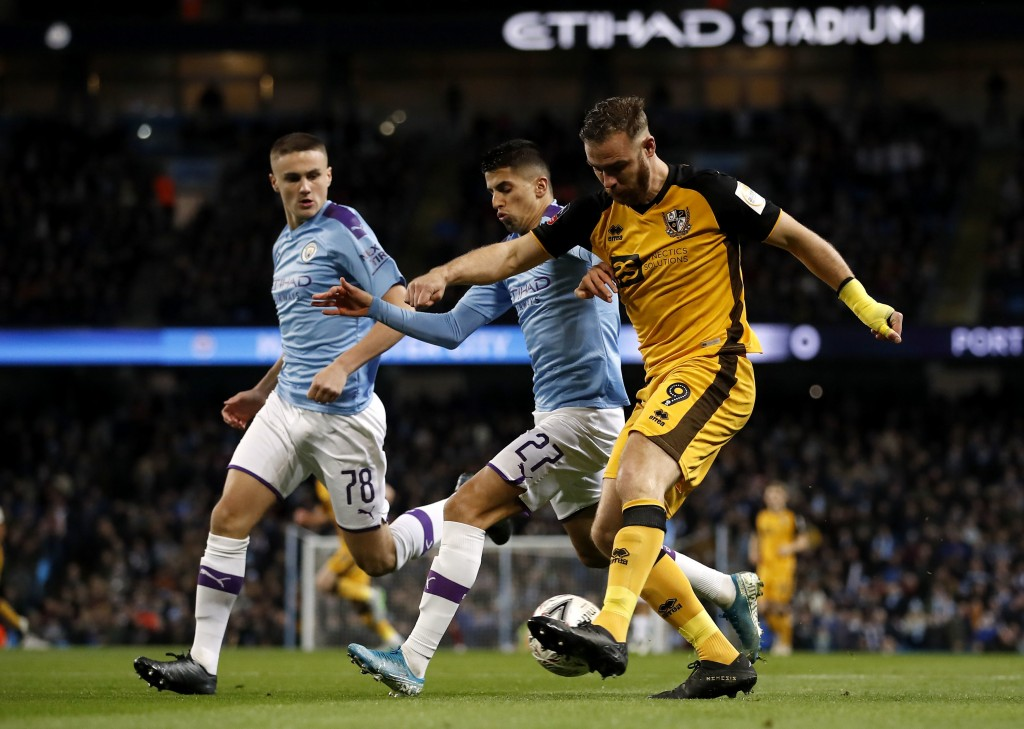 Manchester City's Taylor Harwood-Bellis, left, and Joao Cancelo battle for the ball with Port Vale's Tom Pope, right, during the English FA Cup third ...