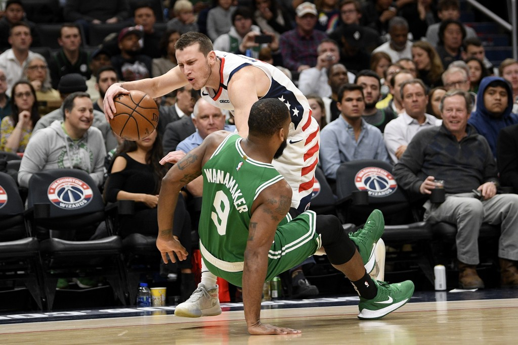 Boston Celtics guard Brad Wanamaker (9) was charged for a foul against Washington Wizards guard Garrison Mathews, back, during the first half of an NB...