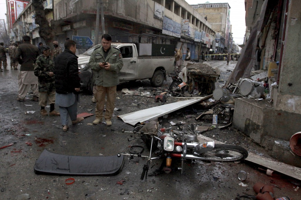 Pakistani police officers examine the site of a bomb explosion in Quetta, Pakistan, Tuesday, Jan. 7, 2020. A powerful roadside bomb exploded near a ve...