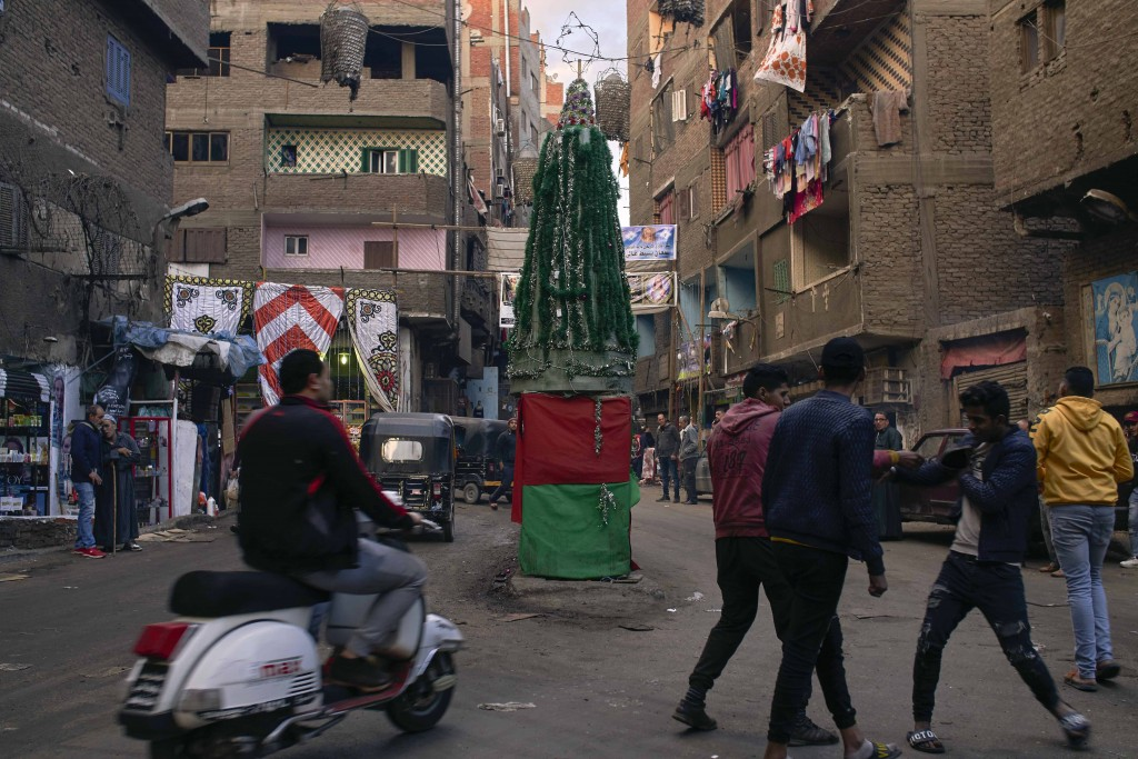 Residents pass by a Christmas tree made of recycled plastic and other material in a Coptic residential and industrial area of eastern Cairo, Egypt, Mo...