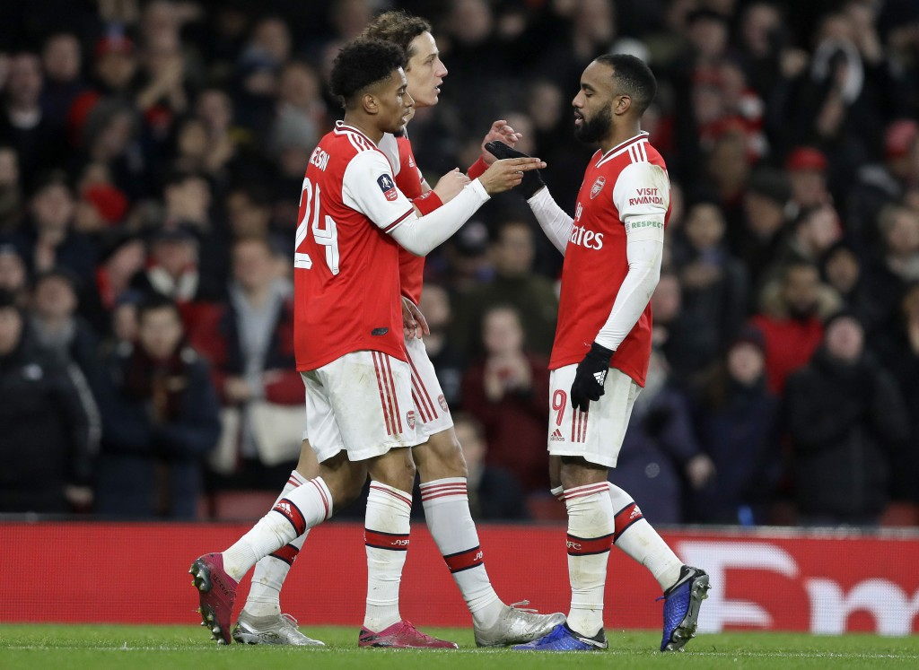 Arsenal's Reiss Nelson, left, celebrates with teammates after scoring his side's first goal during the English FA Cup soccer match between Arsenal and...