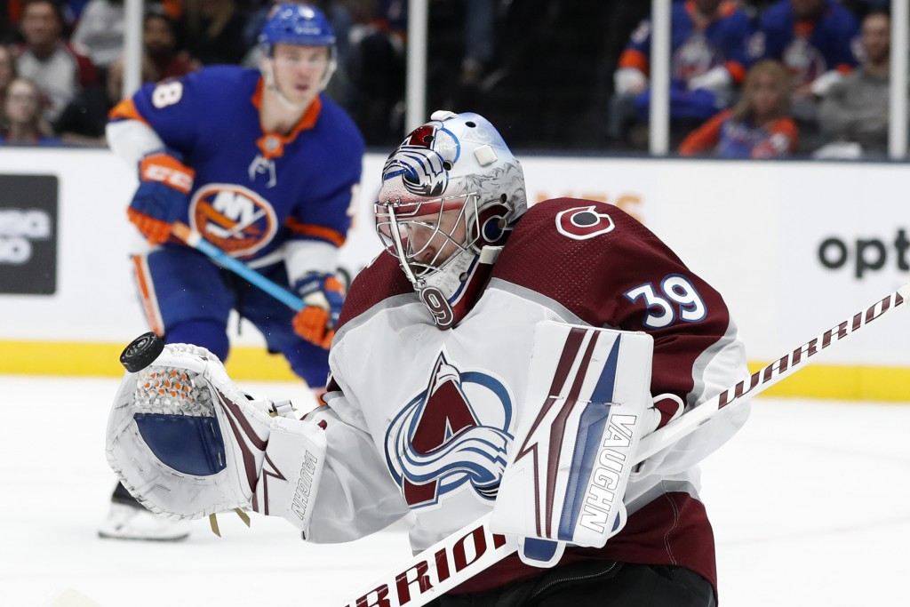 Colorado Avalanche goaltender Pavel Francouz (39) makes a save as New York Islanders defenseman Noah Dobson (8) watches during the second period of an...