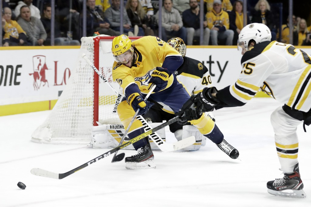 Nashville Predators right wing Craig Smith (15) battles for the puck with Boston Bruins defenseman Brandon Carlo (25) in the second period of an NHL h...
