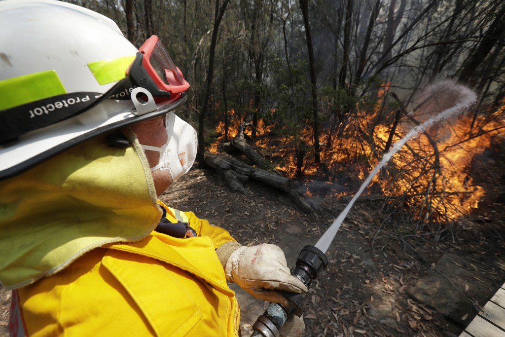 FILE - In this Dec. 8, 2019 file photo a firefighter controls a backburn near Mangrove Mountain, north of Sydney, Australia. U.S. officials said Tuesd...