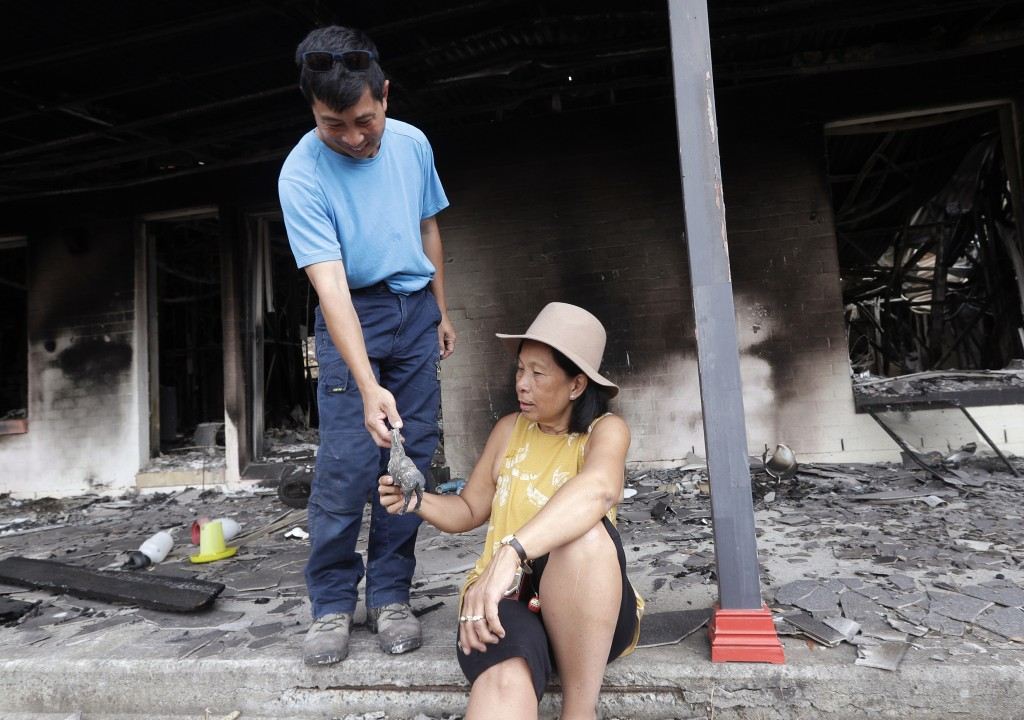 Justin Kam, left, hands to his partner Helena Wong a small horse statue found in the the rubble of their destroyed home at Balmoral, Australia, Tuesda...
