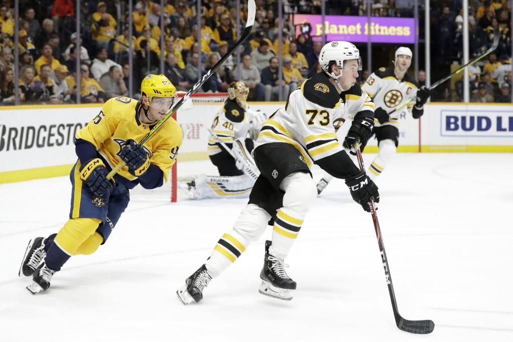 Boston Bruins defenseman Charlie McAvoy (73) moves the puck ahead of Nashville Predators center Matt Duchene (95) in the second period of an NHL hocke...
