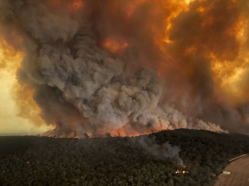 FILE - In this Monday, Dec. 30, 2019, aerial file photo, wildfires rage under plumes of smoke in Bairnsdale, Australia. U.S. officials said Tuesday, J...