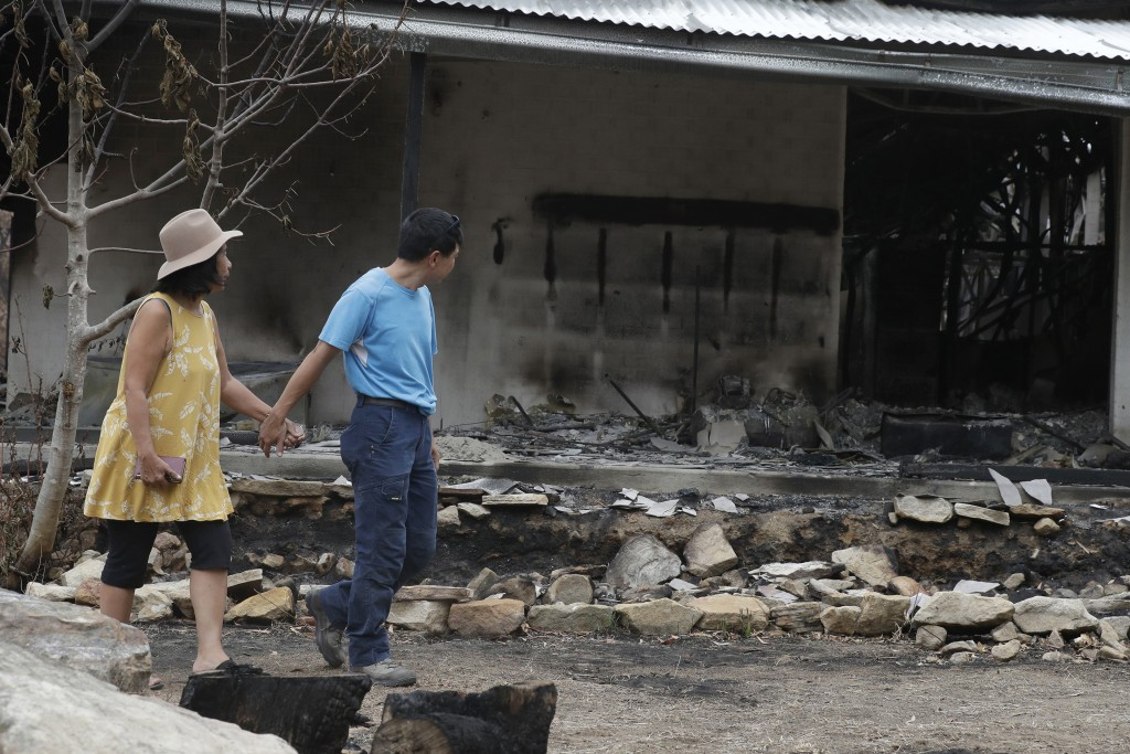 Justin Kam, right, and Helena Wong survey their destroyed home at Balmoral, Australia, Tuesday, Jan. 7, 2020. Kam and Wong built their home with quart...