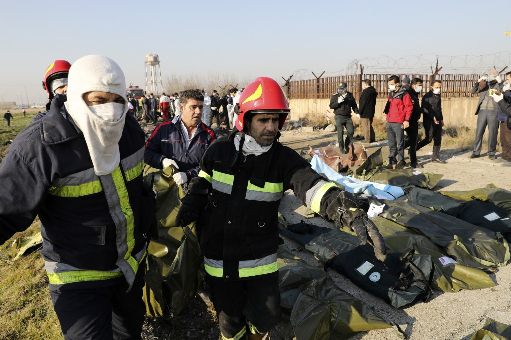 Rescue workers carry the body of a victim of an Ukrainian plane crash in Shahedshahr, southwest of the capital Tehran, Iran, Wednesday, Jan. 8, 2020. ...